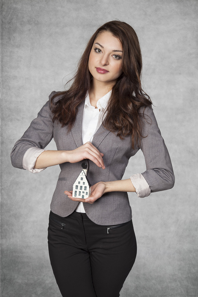 A woman in a business suit holding a house made from card in her hands.